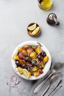 Insalata tiepida di patate con olive, pepe, prezzemolo e cipolla rossa sul vecchio piatto in ceramica bianca su una superficie di cemento grigio