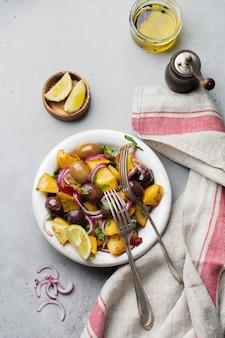 Insalata di patate calda con olive, pepe, prezzemolo e cipolla rossa sul vecchio piatto in ceramica bianca