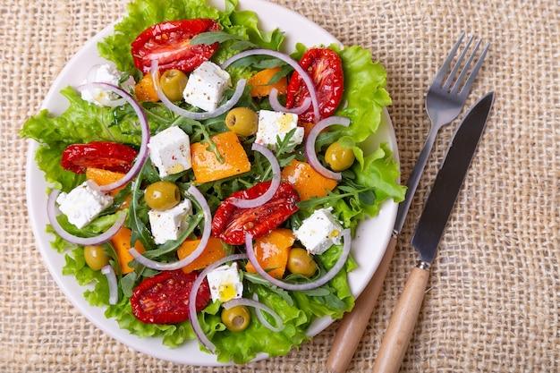 Insalata tiepida con zucca, feta, pomodori secchi, olive, rucola e cipolla rossa. avvicinamento.
