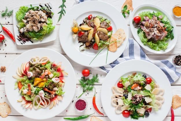 Assortimento di insalate calde sul tavolo del ristorante laici piatta. vista dall'alto sul buffet con varietà di carne laterale
