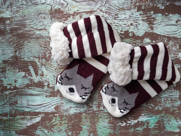Calzini caldi per un inverno freddo con pelliccia e strisce una punta con una faccia di gatto vista dall'alto su uno sfondo eterogeneo