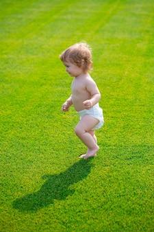 Calda primavera nel parco bambino in un bellissimo campo verde primaverile primo passo