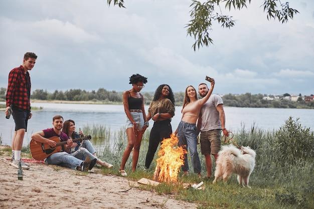 Estate calda. un gruppo di persone fa un picnic sulla spiaggia. gli amici si divertono durante il fine settimana.