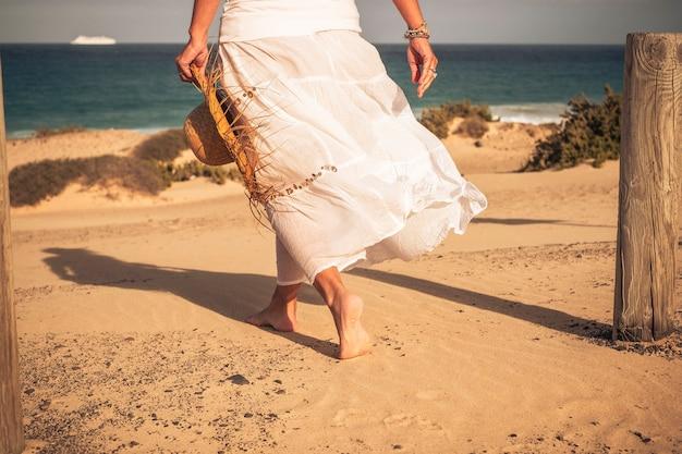 Calda vacanza estiva viaggio vacanza nel concetto di resort paradiso spiaggia con bella donna elegante vista dal retro salking a piedi nudi sulla sabbia godendo l'acqua di mare e all'aperto