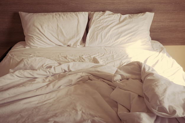 Calda luce del sole su lenzuola e cuscini bianchi disordinati in camera da letto, disordinato letto disordinato dopo il sonno comfort