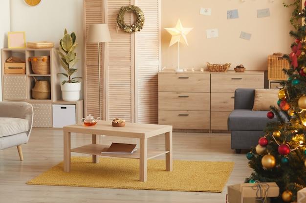 Immagine di sfondo dai toni caldi dell'interno accogliente del soggiorno con albero di natale decorato con dettagli dorati, copia dello spazio
