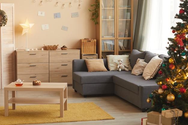 Immagine di sfondo dai toni caldi del soggiorno accogliente con albero di natale decorato con dettagli dorati, copia dello spazio