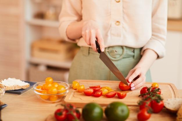 Dai toni caldi close up di irriconoscibile donna che taglia i pomodori freschi durante la cottura sana colazione nell'accogliente cucina interna