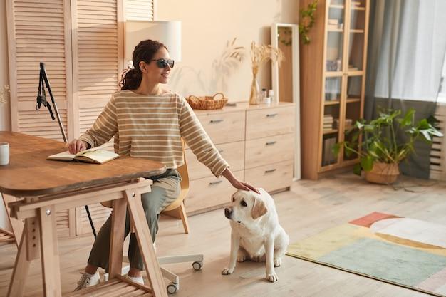 Ritratto a figura intera dai toni caldi di una moderna donna cieca seduta a tavola in un accogliente interno di casa e petting cane guida, spazio copia