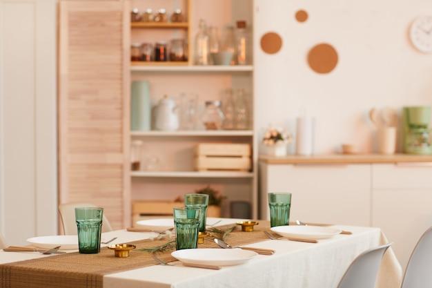 Immagine dai toni caldi dell'interno della cucina accogliente con tavolo servito in primo piano