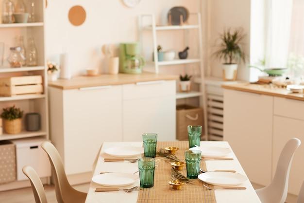 Immagine dai toni caldi dell'interno della cucina minima con tavolo servito in primo piano