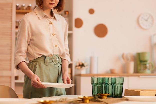 Ritratto di metà sezione dai toni caldi del tavolo da servizio di giovane donna nell'interno della cucina minima