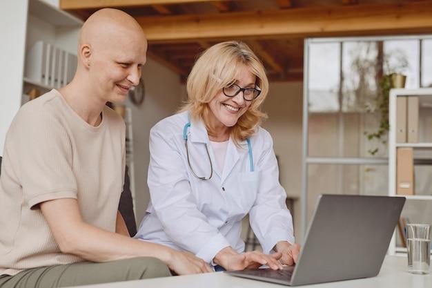 Dai toni caldi ritratto di allegro medico donna utilizzando laptop e parlando con paziente calvo durante la consultazione su alopecia e recupero del cancro, spazio di copia