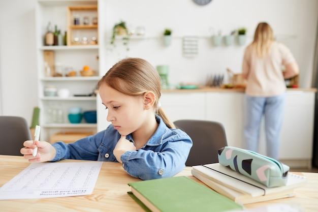 Ritratto dai toni caldi della bambina sveglia che fa i compiti mentre è seduto alla scrivania in interni accoglienti con la madre sullo sfondo, lo spazio della copia