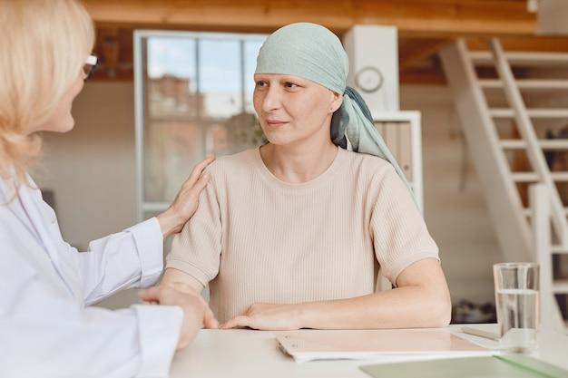 Dai toni caldi ritratto di donna calva matura parlando al medico donna confortante e congratulandosi con lei durante la consultazione su alopecia e recupero del cancro, spazio di copia