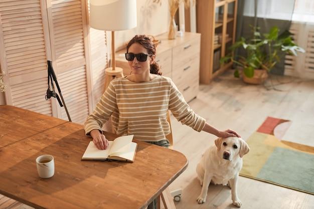 Dai toni caldi ritratto di una moderna donna cieca che legge un libro in braille mentre è seduto a tavola in un accogliente interno di casa e accarezza il cane guida, spazio di copia