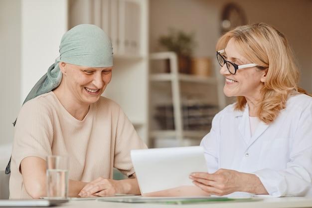 Dai toni caldi ritratto di sorridente donna calva ascoltando medico donna che mostra risultati negativi dei test durante la consultazione su alopecia e recupero del cancro, spazio di copia