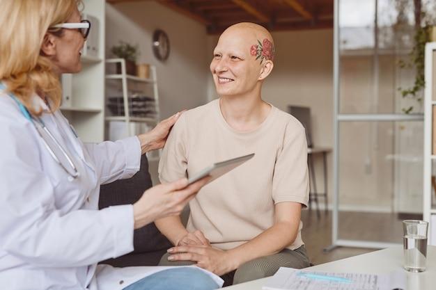Ritratto dai toni caldi della donna calva sorridente che parla alla dottoressa durante la consultazione su alopecia e recupero del cancro, copia dello spazio