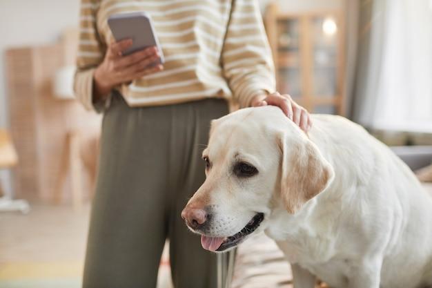 Ritratto dai toni caldi del cane labrador bianco seduto sul letto di casa e che si gode gli animali domestici dal proprietario femminile, copia spazio