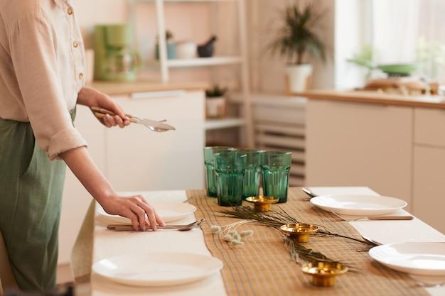 Tonica calda vista laterale ritratto di giovane donna che serve tavolo in cucina minimal interno