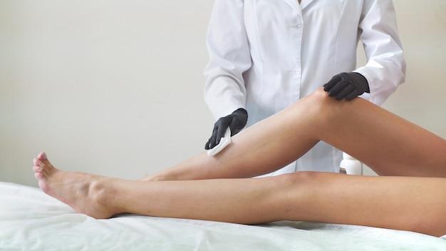 Cera calda sui piedi delle donne, depilazione professionale in studio
