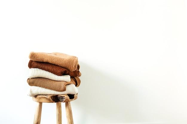 Maglioni lavorati a maglia di lana femminili caldi di inverno, pila di pullover sullo sgabello di legno al bianco. concetto di vestiti moderni per riviste, blog, social media.