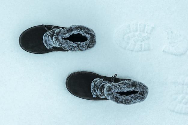 Caldi stivali di pelliccia da donna che camminano nella neve. la vista dall'alto. scarpe invernali da donna belle e pratiche.