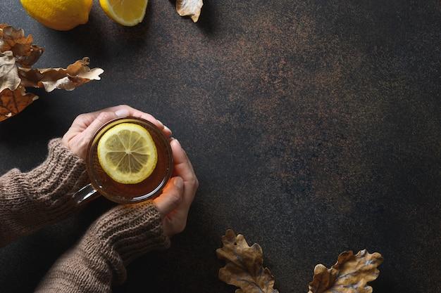 Tè caldo al limone nelle mani della donna in maglione di lavoro a maglia sullo spazio marrone