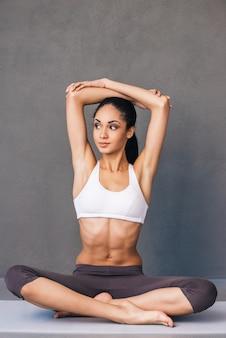 Riscaldamento. bella giovane donna africana in abbigliamento sportivo che pratica yoga mentre è seduta nella posizione del loto su sfondo grigio