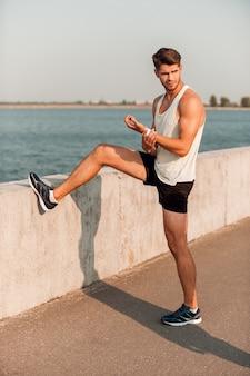 Riscaldarsi prima di fare jogging. bel giovane uomo muscoloso che si scalda prima di correre stando in piedi all'aperto