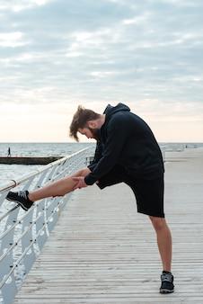 Riscaldando la vista laterale del ritratto integrale dell'uomo di forma fisica vicino al mare