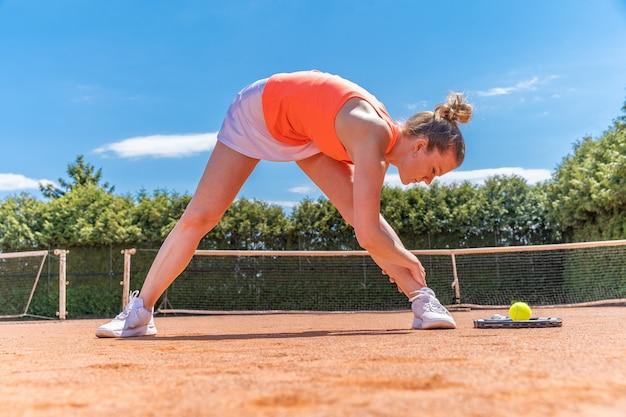 Riscaldamento e stretching prima di una partita di tennis in campo.