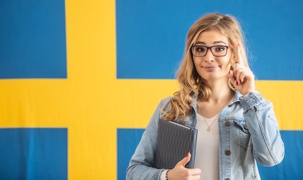 Dito d'avvertimento alzato da una bionda con gli occhiali in piedi davanti alla bandiera svedese.