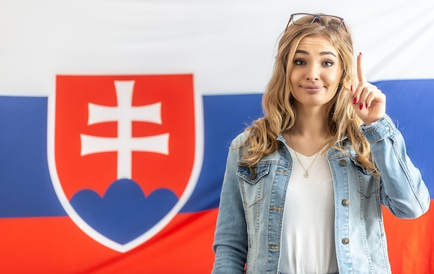 Avvertimento dito alzato da una ragazza bionda in piedi davanti alla bandiera della slovacchia.