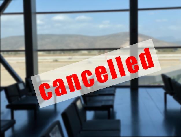 Un segnale di avvertimento che il volo è cancellato su un territorio sfocato dell'aeroporto.