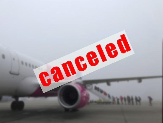 Un segnale di avvertimento che l'aereo è cancellato su un aereo sfocato all'aeroporto.