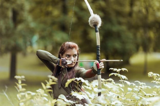 Donna medievale guerriero con arco da caccia nella foresta verde, primo piano