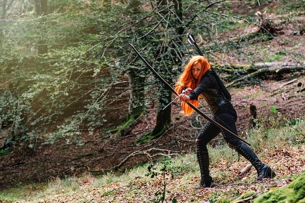 Donna medievale guerriera con l'arco che caccia nella foresta misteriosa