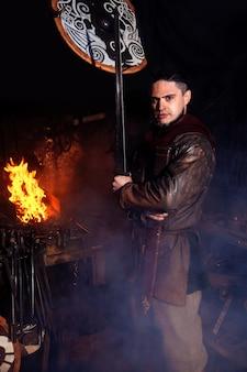 Il guerriero vichingo è vicino al fuoco nella sua fucina con le armi in mano.