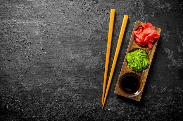 Wasabi, zenzero marinato e salsa di soia in un supporto di legno con le bacchette. sulla tavola rustica nera