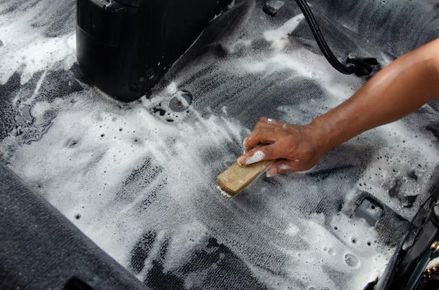 Lavare il tappeto dell'auto.dettagli sull'interno dell'auto moderna.pulire utilizzando una spazzola e una soluzione detergente sul tappeto dell'auto.