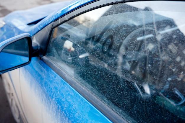 Lava il vetro sporco e polveroso del finestrino di un'auto