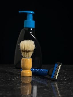 Gel detergente, pennello da barba e rasoio su uno sfondo di pietra. set per la cura del viso di un uomo.