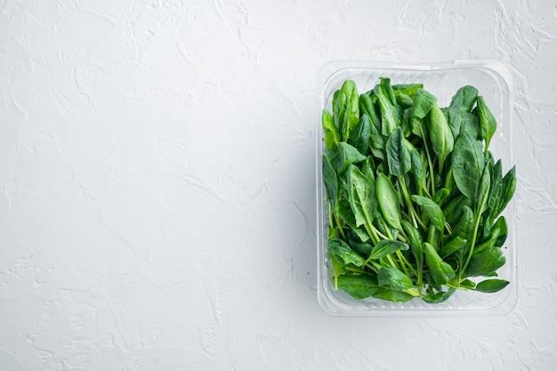 Set di mini spinaci freschi lavati, su sfondo bianco, in confezione di plastica, vista dall'alto piatta, con spazio per copyspace di testo