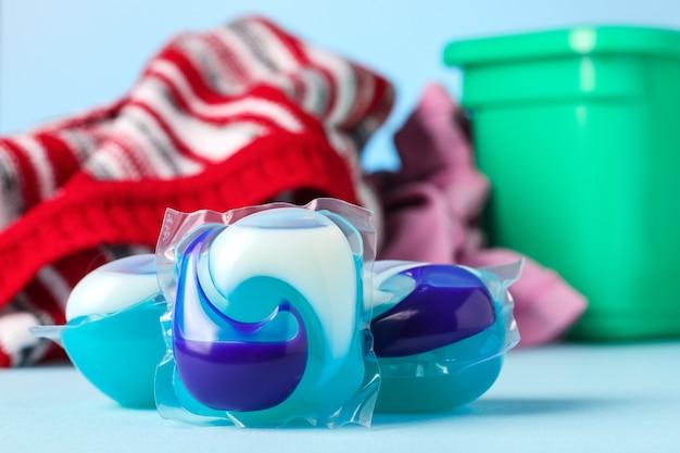 Capsule di lavaggio contro il mucchio di vestiti sulla superficie blu, piccola profondità di messa a fuoco.