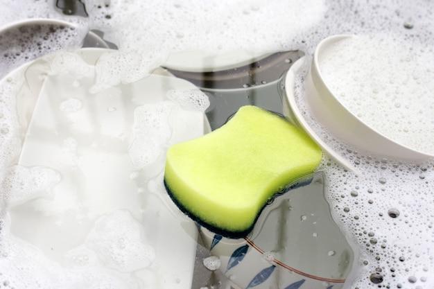 Lavare i piatti, close up di utensili in ammollo nel lavello da cucina.