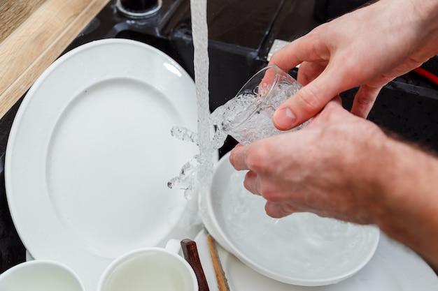 Lavare i piatti - mani dell'uomo nei guanti che risciacquano il vetro sotto l'acqua corrente nel lavandino.