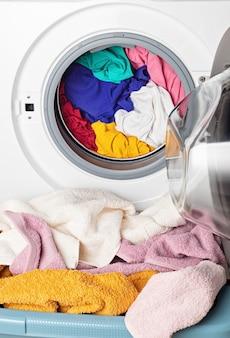 Lavatrice o asciugatrice caricata con la biancheria. lavaggio, concetto di pulizie di primavera