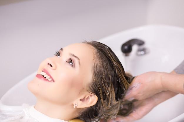 Procedura di lavaggio dei capelli. la cliente sta riposando mentre i suoi capelli vengono puliti dall'hairstylist.