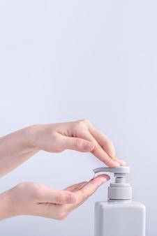 Lavarsi le mani. giovane donna asiatica che usa sapone liquido per lavarsi le mani, concetto di igiene per smettere di diffondere il coronavirus isolato su sfondo bianco grigio, primo piano.